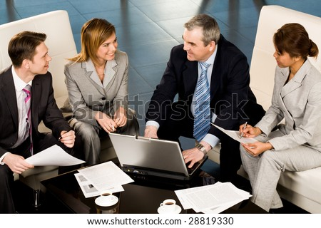 Portrait of several employees looking at their senior boss during teamwork