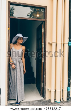 Portrait of sexy fit lady in summer dress and straw hat posing for the camera near entrance with stairs. Beauty cute girl in a tropical resort. Outdoor lifestyle portrait on hot sunny summer day.
