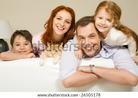 Portrait of siblings and their parents with cute cat looking at camera
