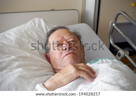 Portrait of sick old man in hospital bed