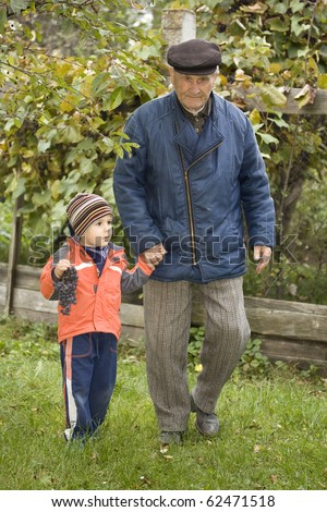 Portrait of small boy helping a old man on walking - Outdoor