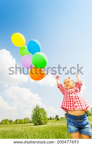 Portrait of small cute girl with many balloons