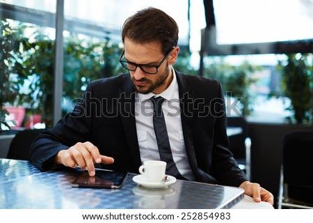 Portrait of smart and handsome businessman using a digital tablet while sitting at a table in coffee shop, business and technology concept