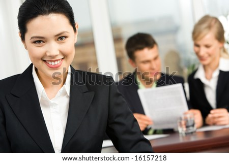 Portrait of smiling Asian woman on the background of working business team