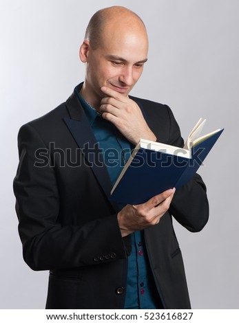 portrait of smiling bald guy reading a book. Studio shot