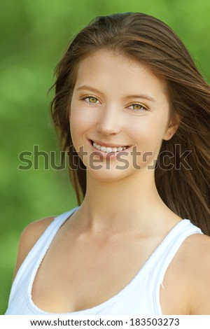 Portrait of smiling beautiful young woman close up, against background of summer green park.