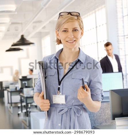 Portrait of smiling blonde businesswoman holding files, looking at camera.