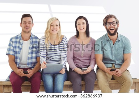 Portrait of smiling business people holding electronic gadgets against grey vignette