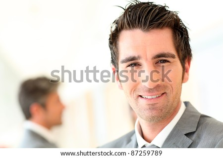 Portrait of smiling businessman standing in hall