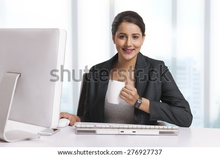 Portrait of smiling businesswoman having coffee at desk in office
