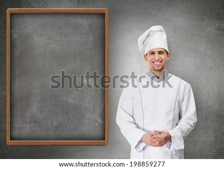 Portrait of smiling chef cook standing near grey menu blackboard, isolated on grey