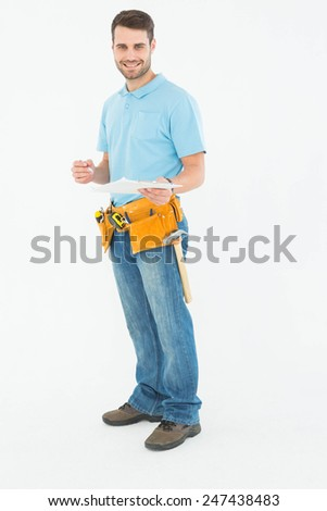 Portrait of smiling construction worker holding clipbard over white background