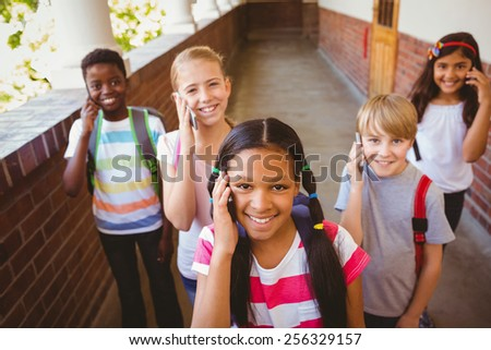 Portrait of smiling little school kids using cellphones in school corridor