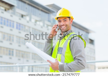 Portrait of smiling male architect with blueprints talking on mobile phone outdoors