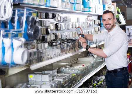 Portrait of smiling man selecting electric socket in household department