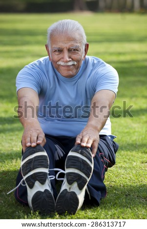 Portrait of smiling man stretching in park