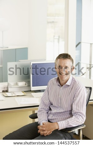 Portrait of smiling middle aged male executive sitting on chair at desk