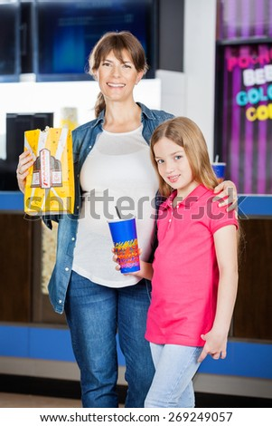 Portrait of smiling mother and daughter holding popcorn and drink in cinema