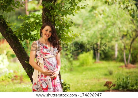 portrait of smiling pregnant  woman with hands over tummy in the park in summer