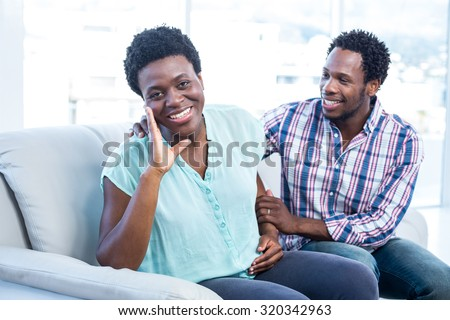 Portrait of smiling pregnant woman with her partner sitting on sofa