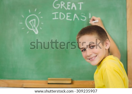 Portrait of smiling pupil writing on chalkboard in a classroom in school