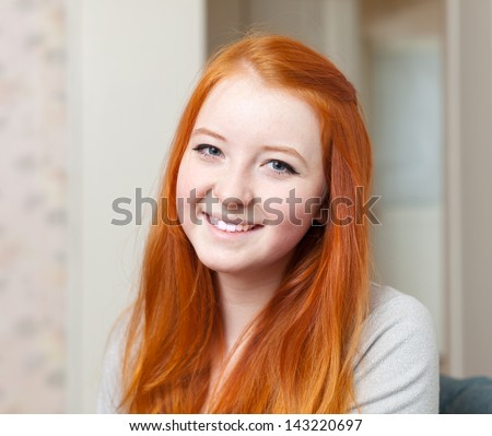 Portrait of smiling red-haired tenager girl in home