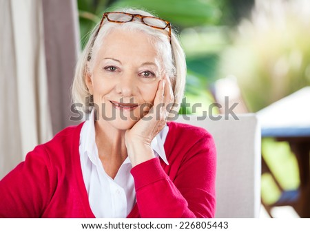 Portrait of smiling senior woman with hand on chin sitting at nursing home