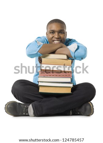 Portrait of smiling teenage guy with pile of books against white background