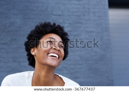 Portrait of smiling young african woman looking away at copy space