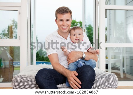 Portrait of smiling young father with child sitting on couch