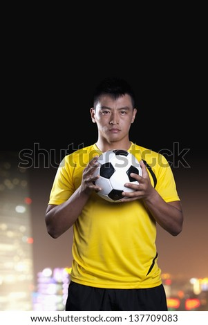 Portrait of soccer player holding a soccer ball, background at night