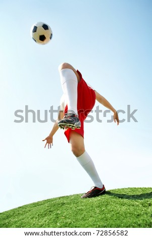 Portrait of soccer player kicking ball by knee on football field