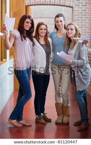 Portrait of students having their results in a corridor
