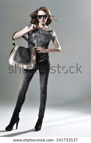 Portrait of stylish woman holding bag walking-full body