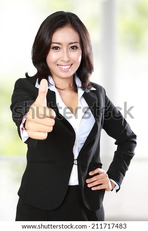 portrait of successful businesswoman showing thumb up to camera