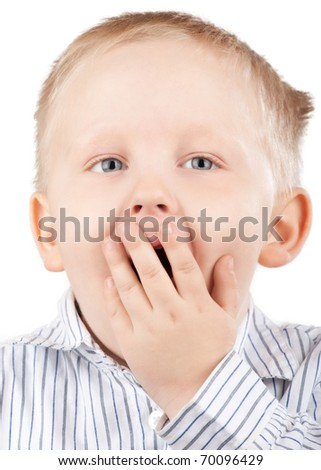 Portrait of surprised little boy with blond hair covering his mouth by his hand