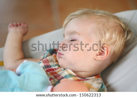 Portrait of sweet baby girl sleeping cozy in a bouncer holding a doll