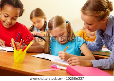 Portrait of teacher looking at a drawing schoolgirl�¢??s copybook at lesson