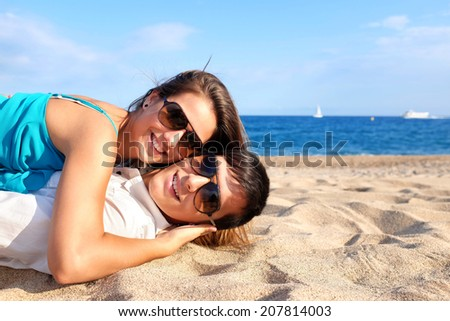 Portrait of teen Couple laying together on beach.
