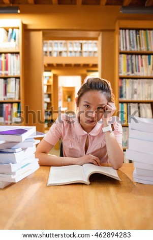 Portrait of tensed young woman studying in library at college