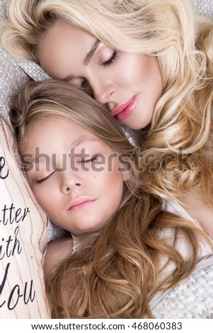 Portrait of the beautiful blonde woman mother and daughter on the beautiful face and amazing eyes lie sleeping on a bed in an elegant linen, hug each other and smile joyfully