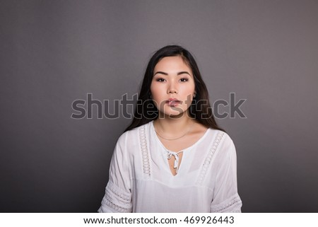 Portrait of the beautiful elegant girl model student in jeans and a white jacket Asian appearance in a studio on a dark gray background sitting on a chair. Street casual casual style