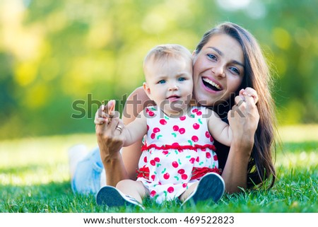 portrait of the beautiful toddler and her mother on the grass in the park