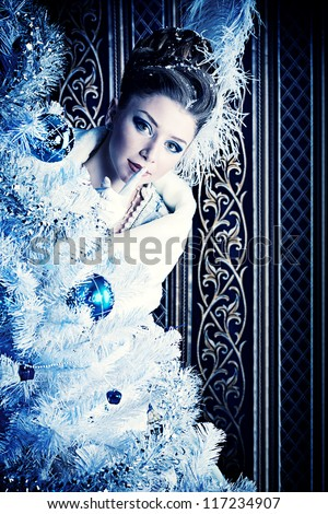 Portrait of the elegant woman posing with Christmas tree over vintage background.