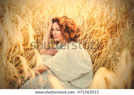 Portrait of the middle aged beautiful smiling woman in wheat field. instagram image filter retro style