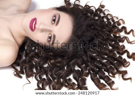 Portrait of the pretty young woman with beauty curly on the floor, isolated on the white background