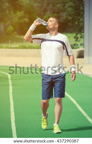 Portrait of thirsty sportsman drinking water from the plastic bottle and walking on the green running track. Ideal for bottle pack shoot adding.  Sport, fitness, jogging, healthy lifestyle concepts