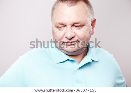Portrait of thoughtful aged man wearing blue shirt looking aside standing against white wall - dreams concept
