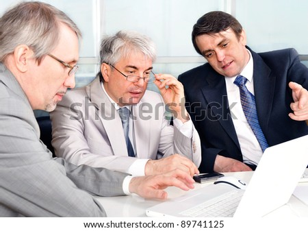 Portrait of three businessmen at the computer. Office background.