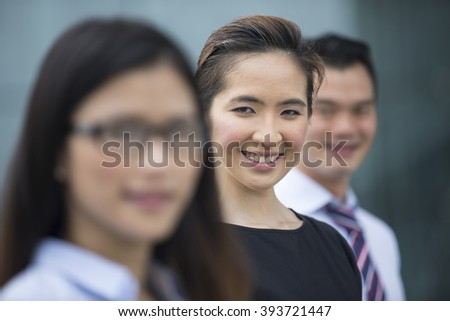 Portrait of three Chinese business colleagues in a modern urban setting.  Focus is on the woman in the middle.